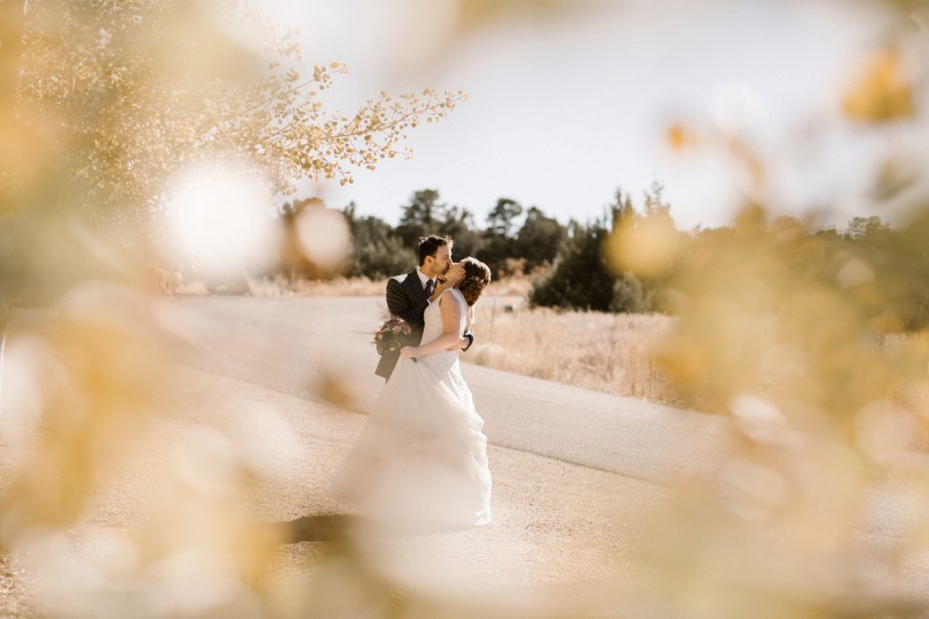 Bride and groom embracing and kissing along road