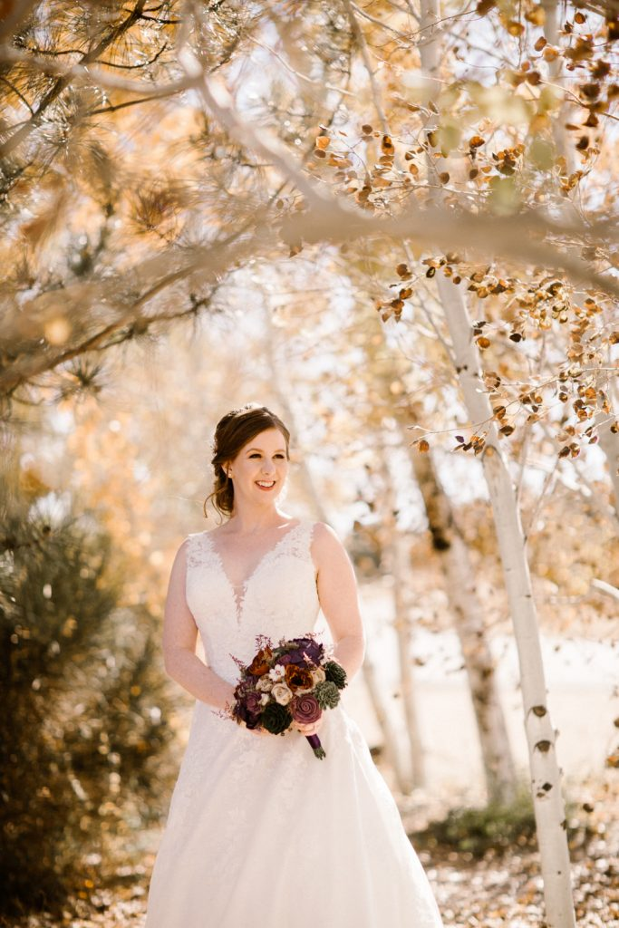 Bride posing with bouquet under trees