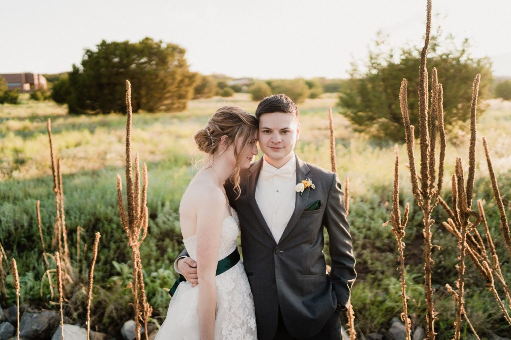 Bride and groom posing in field of plants and flowers