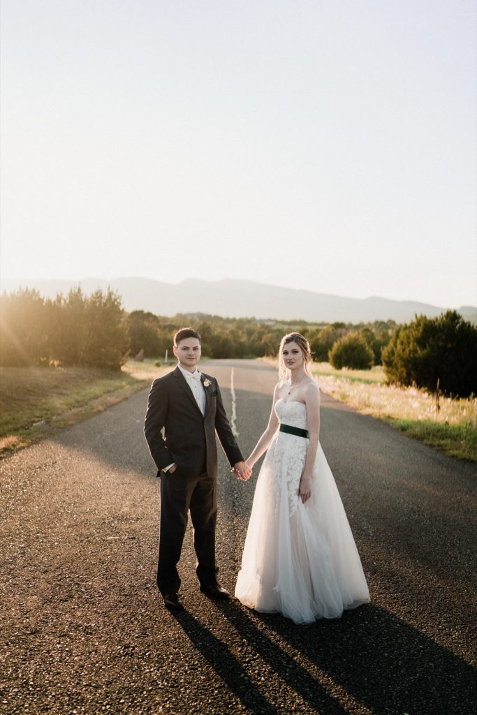 Bride and groom posing in the middle of a road